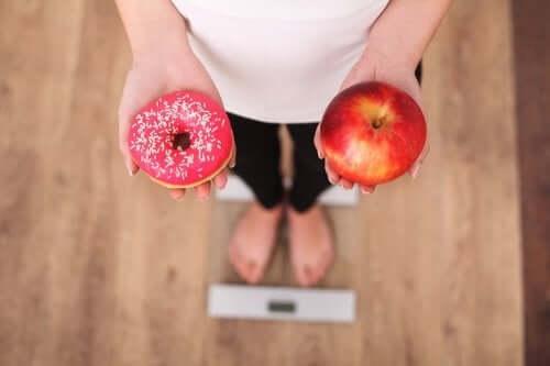 Γυναίκα κρατά ντόνατ και μήλο