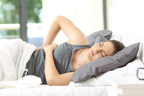 Γυναίκα στο κρεβάτι με πόνο στην πλάτη
