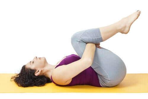 Γυναίκα ξαπλωμένη με τα γόνατα λυγισμένα προς το στήθος