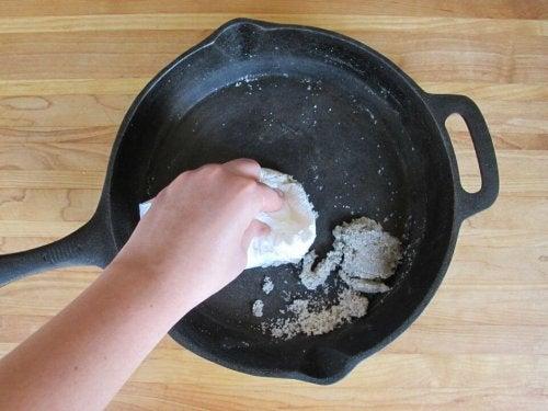 Άτομο καθαρίζει τηγάνι με αλάτι
