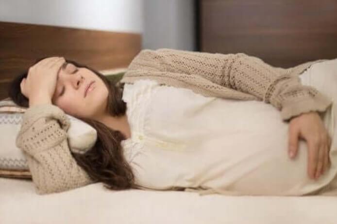έγκυος ξαπλωμένη σε κρεβάτι