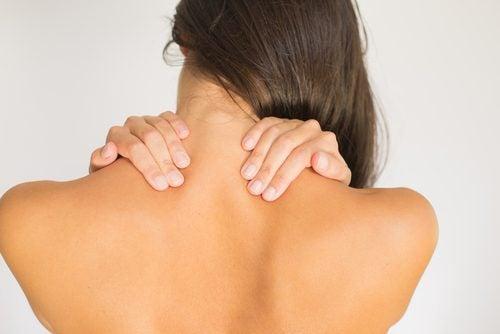 Γυναίκα ακουμπά την πλάτη της με τα χέρια της