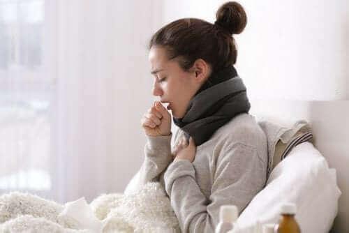 Γυναίκα στο κρεβάτι βήχει-  για να ξεπεράσετε το κρυολόγημα
