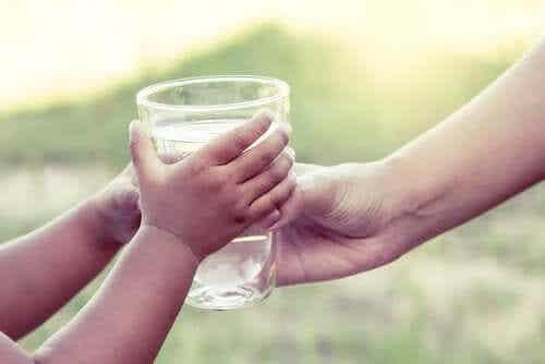Γυναίκα δίνει ποτήρι με νερό σε παιδί