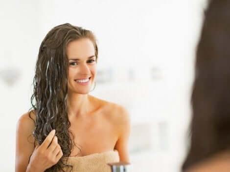 Γυναίκα κοιτάζεται στον καθρέφτη μετά από το μπάνιο