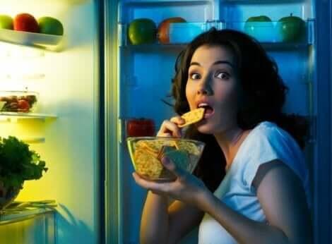 Γυναίκα τρώει μπροστά στο ψυγείο