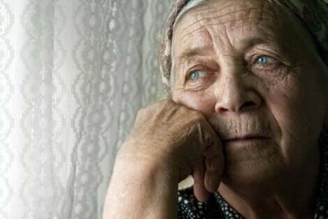 Ηλικιωμένη γυναίκα κοιτά από το παράθυρο
