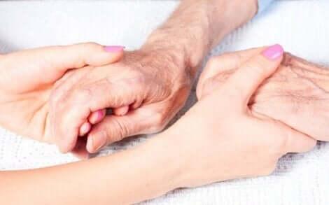 Νεαρή γυναίκα κρατά τα χέρια ηλικιωμένου ατόμου