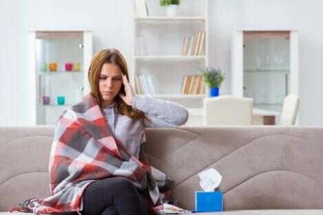 Άρρωστη γυναίκα κάθεται σε καναπέ