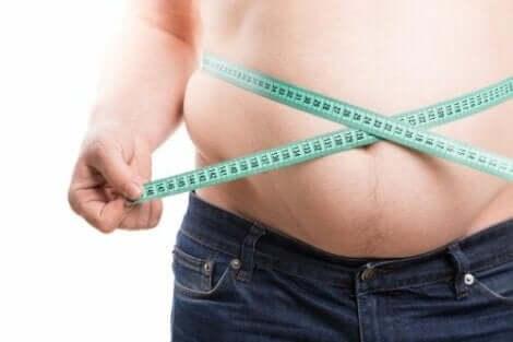 Παχύσαρκος άνδρας μετρά την κοιλιά του