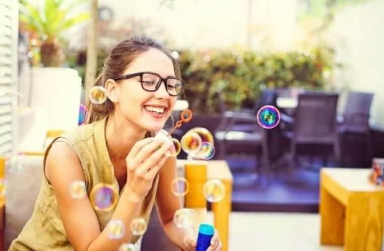 γυναίκα παίζει με σαπουνόφουσκες