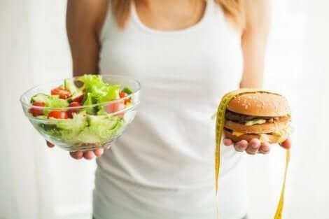 Γυναίκα κρατά μια σαλάτα και ένα burger