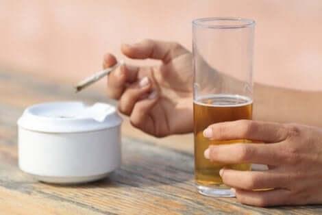 Άτομο κρατά ποτό και τσιγάρο