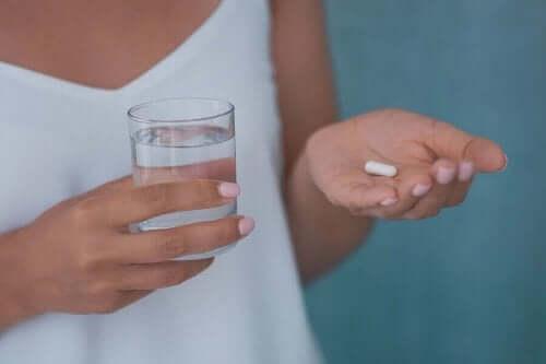 Γυναίκα κρατά ένα χάπι και ένα ποτήρι νερό ολανζαπίνη