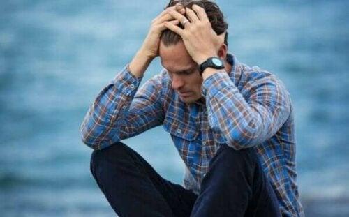 Άνδρας λυπημένος πιάνει το κεφάλι του