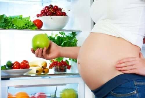Έγκυος μπροστά σε ψυγείο κρατά μήλο