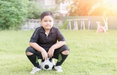Παιδί κάθεται πάνω σε μπάλα ποδοσφαίρου