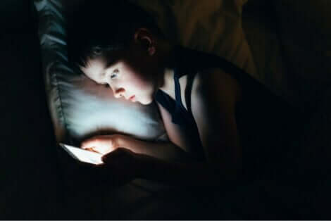 Παιδί στο κρεβάτι κρατά κινητό
