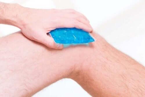 Άνδρας εφαρμόζει κρύα κομπρέσα στο πόδι του