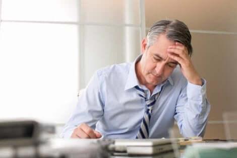 Άνδρας στο γραφείο πιάνει το κεφάλι του