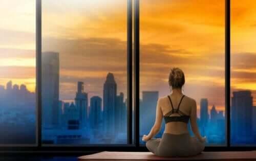Γυναίκα κάνει γιόγκα κοιτάζοντας την πόλη