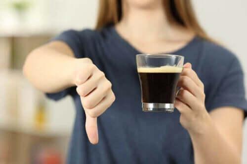 Γυναίκα κρατά ποτήρι με καφέ και λέει όχι