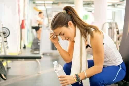Γυναίκα στο γυμναστήριο κρατά μπουκάλι με νερό