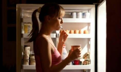 Γυναίκα τρώει μπροστά σε ανοιχτό ψυγείο