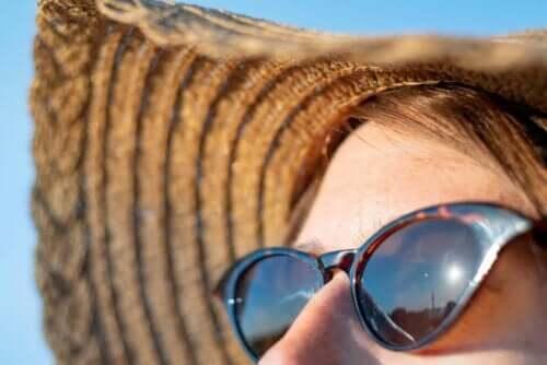 Γυναίκα φορά γυαλιά ηλίου και καπέλο