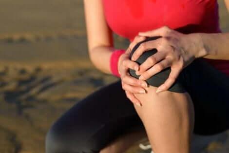 Γυναίκα πιάνει το γόνατό της