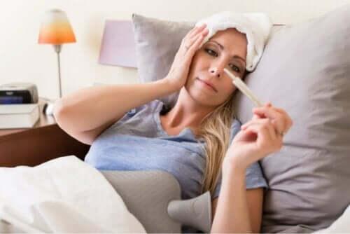 Γυναίκα ξαπλωμένη κοιτά θερμόμετρο