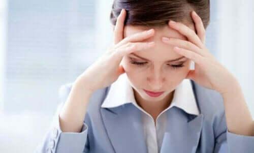 Γυναίκα αγχωμένη κρατά το κεφάλι της
