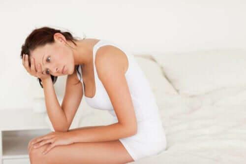 Γυναίκα κάθεται στο κρεβάτι στεναχωρημένη-έγκαιρη αντιμετώπιση μιας ουρολοίμωξης