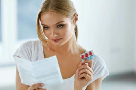 Γυναίκα κρατά χάπια και διαβάζει οδηγίες