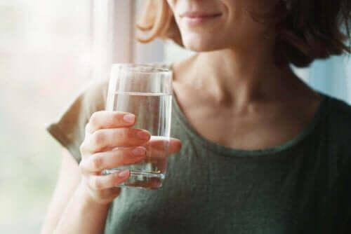 Γυναίκα κρατά ποτήρι με νερό