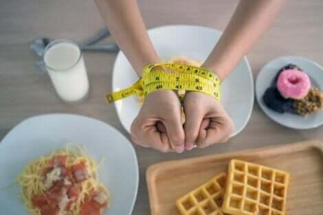 Γυναίκα με δεμένα χέρια πάνω από φαγητά με υδατάνθρακες