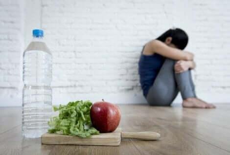 Γυναίκα στη γωνία και φρούτα και λαχανικά στο προσκήνιο- υπερβολική ανησυχία