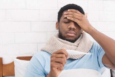 Άνδρας με πυρετό κοιτά θερμόμετρο