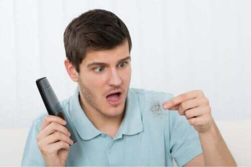 Άνδρας σοκαρισμένος κρατά τούφα μαλλιών και χτένα