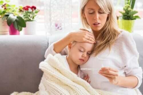 Γυναίκα αγκαλιά με παιδί κοιτά θερμόμετρο