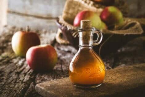 Μηλόξυδο σε γυάλινο μπουκάλι και μήλα
