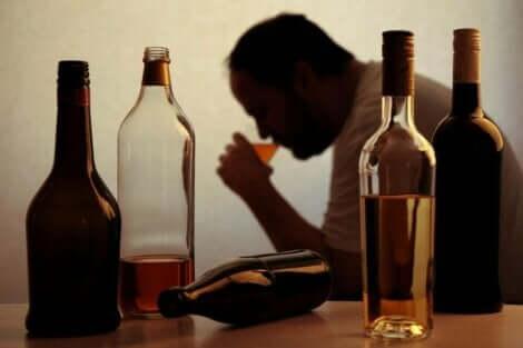 Μπουκάλια άδεια και άνδρας πίνει αλκοόλ