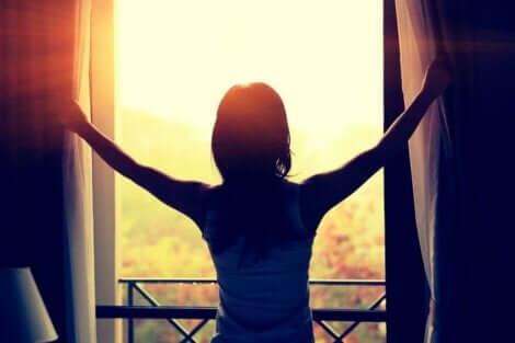 Γυναίκα μπροστά σε παράθυρο ανοίγει κουρτίνες