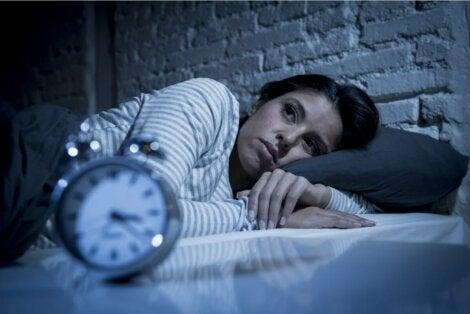 Γυναίκα κοιτάζει το ρολόι δίπλα από το κρεβάτι