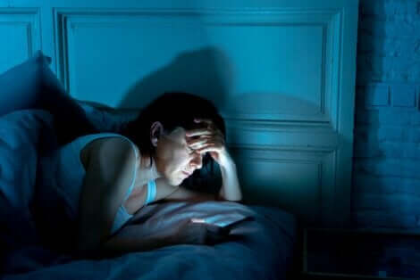 Γυναίκα ασχολείται με το κινητό στο κρεβάτι