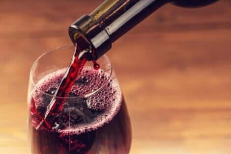 Άτομο βάζει κόκκινο κρασί σε ποτήρι