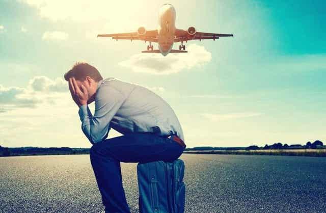 Άνδρας κάθεται σε βαλίτσα ενώ πετά αεροπλάνο από πάνω του