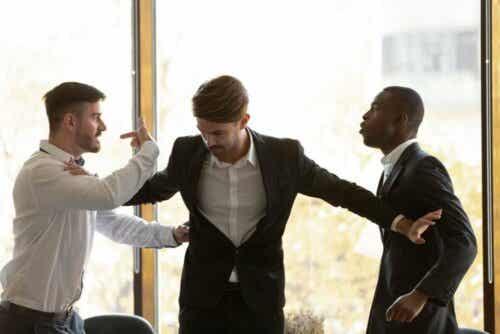 Άνδρας προσπαθεί να χωρίσει δύο θυμωμένους άνδρες