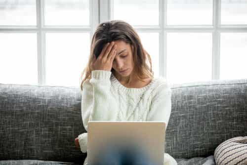 Γυναίκα μπροστά σε υπολογιστή πιάνει το κεφάλι της