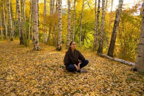 Γυναίκα κάθεται στο έδαφος σε δάσος